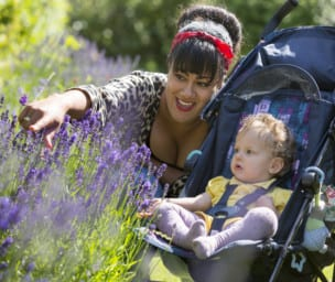 Mother with baby in pram pointing and smiling at the lavender